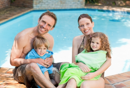 beside: Portrait of a happy family beside the swimming pool Stock Photo