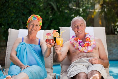 Mature couple drinking a cocktail  beside the swimming pool Stock Photo - 10185089