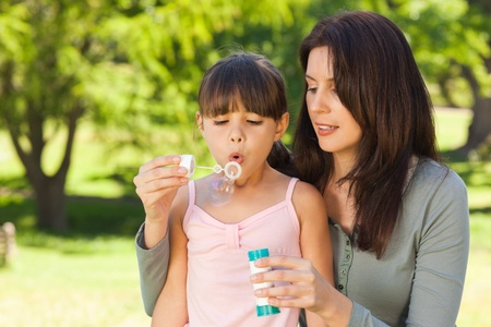 Girl blowing bubbles with her mother in the park Stock Photo - 10197184