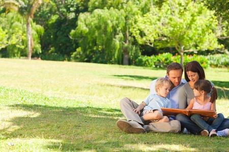 Familia que busca a su álbum de fotos en el parque