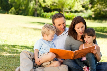 Family looking at their photo album in the park photo