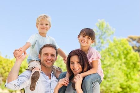 happy family nature: Parents giving  children a piggyback