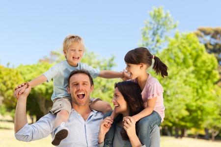 familia en jardin: Los padres dar a los ni�os a cuestas Foto de archivo