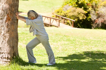 Mature woman doing her streches in the park photo
