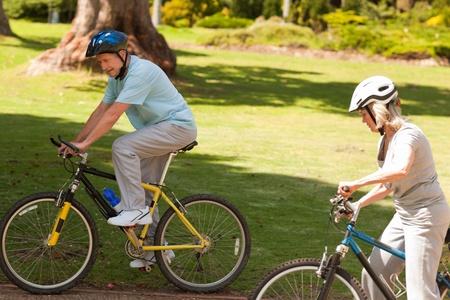 Retired couple mountain biking outside photo