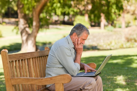 Elderly man working on his laptop in the park photo