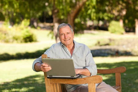 Retired man working on his laptop in the park photo