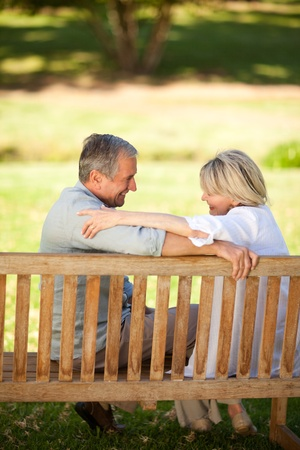 Happy retired couple sitting on the bench photo
