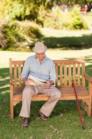 Retired man reading his newspaper on the bench photo