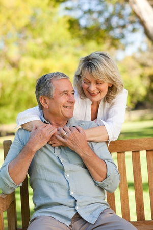 one mid adult man: Senior woman hugging her husband who is on the bench Stock Photo