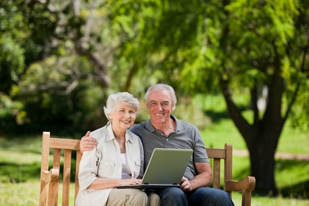 Elderly couple looking at their laptop photo