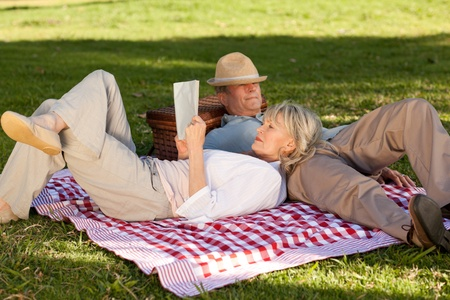 Woman reading while her husband is sleeping in the park photo