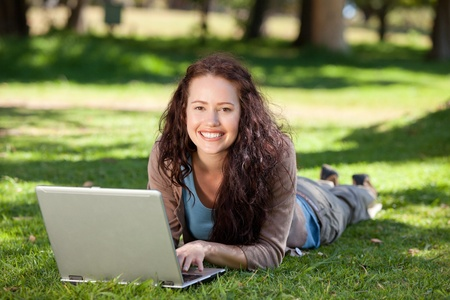 Woman working on her laptop in the park photo