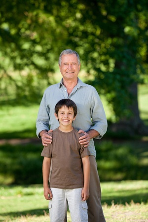 Grandather and his grandson looking at the camera in the park photo