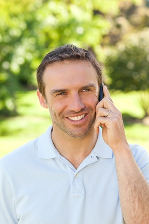 Handsome man phoning in the park photo