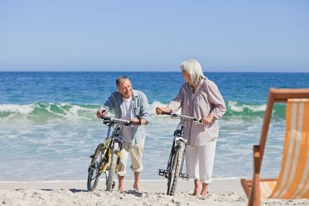 grandfather and grandmother: Elderly couple with their bikes on the beach