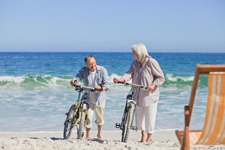 �lteres Paar mit ihren Fahrr�dern am Strand