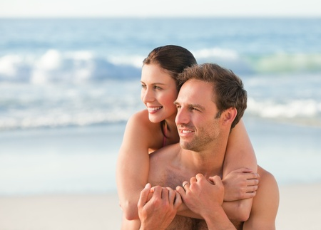 Enamored couple hugging on the beach photo