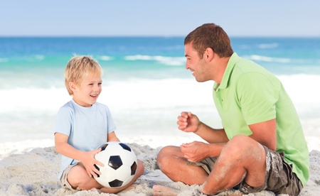 Happy father playing football with his son photo