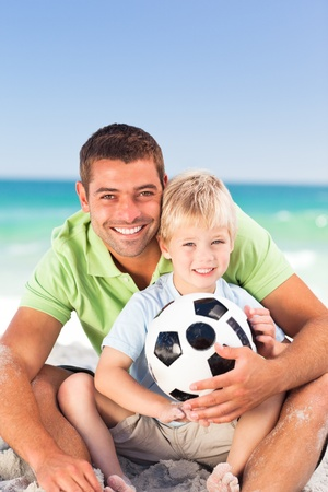 union beach: Happy father playing football with his son