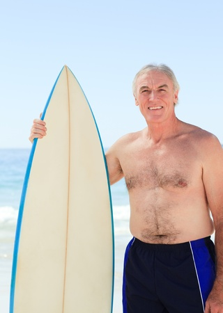 Retired  man with his surfboard photo