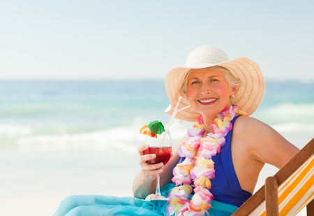 Woman drinking a cocktail in her deck chair photo