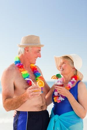 Senior couple drinking a cocktail on the beach photo