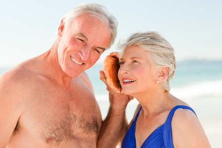 Retired couple listening to their shell Stock Photo - 10197178