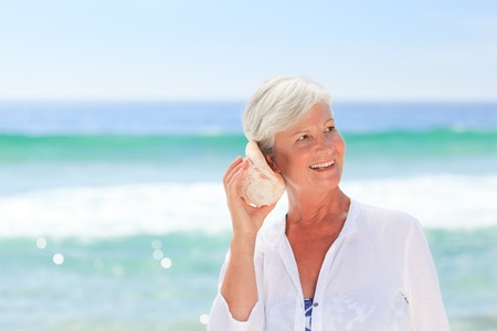 Mature woman listening to her shell photo