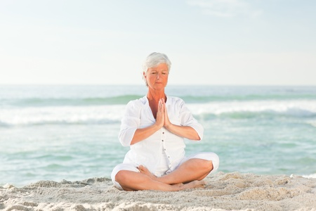 Mature woman practicing yoga on the beach Stock Photo - 10197008