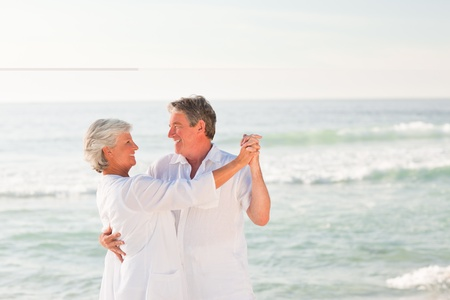 Elderly couple dancing on the beach Stock Photo - 10182622