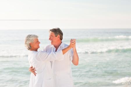 Elderly couple dancing on the beach Stock Photo - 10182622