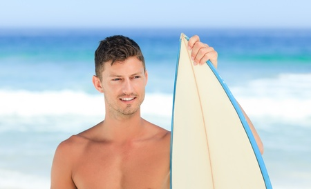 Handsome man with his surfboard Stock Photo - 10195485