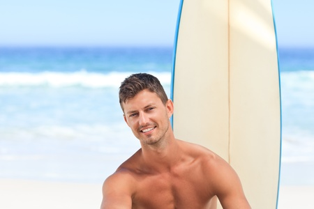Handsome man with his surfboard photo