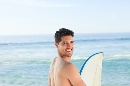 Handsome man beside the sea with his surfboard Stock Photo - 10196991