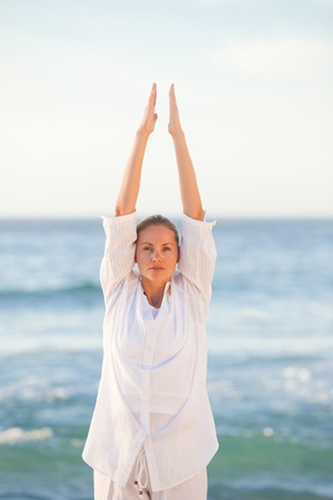 Woman practicing yoga at the beach Stock Photo - 10196776