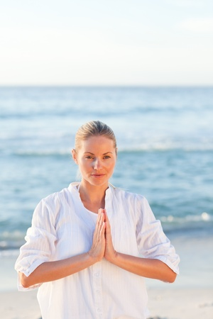 Woman practicing yoga at the beach photo