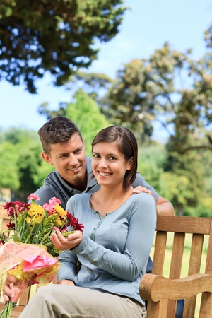 Young man offering flowers to his girlfriend Stock Photo - 10197393