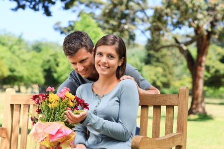 Young man offering flowers to his girlfriend  photo