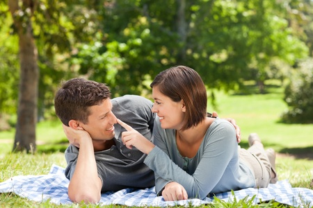 Couple lying down in the park photo