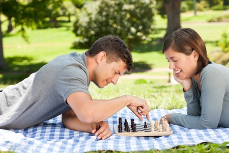 Couple playing chess in the park photo