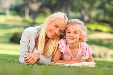 Mother with her daughter lying down in the park photo