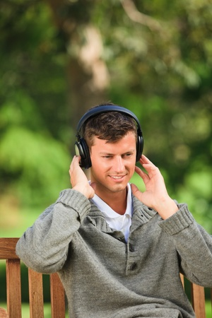 Young man listening to some music on the bench photo