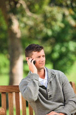 Man phoning on the bench photo