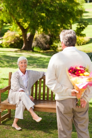 Retired man offering flowers to his wife photo