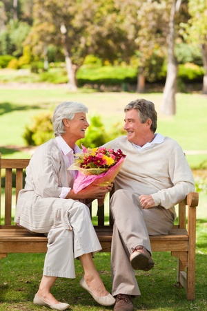 Senior man offering flowers to his wife photo
