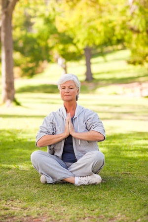 Senior woman practicing yoga in the park photo