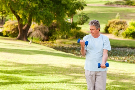 Elderly man doing his exercises in the park Stock Photo - 10190286