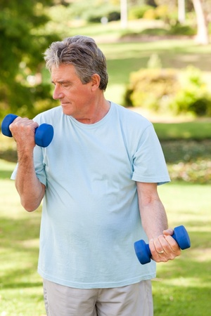 Elderly man doing his exercises in the park photo