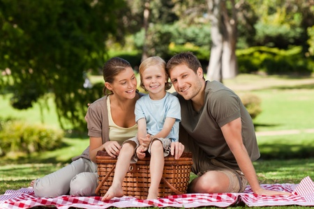 Joyful family picnicking in the park photo